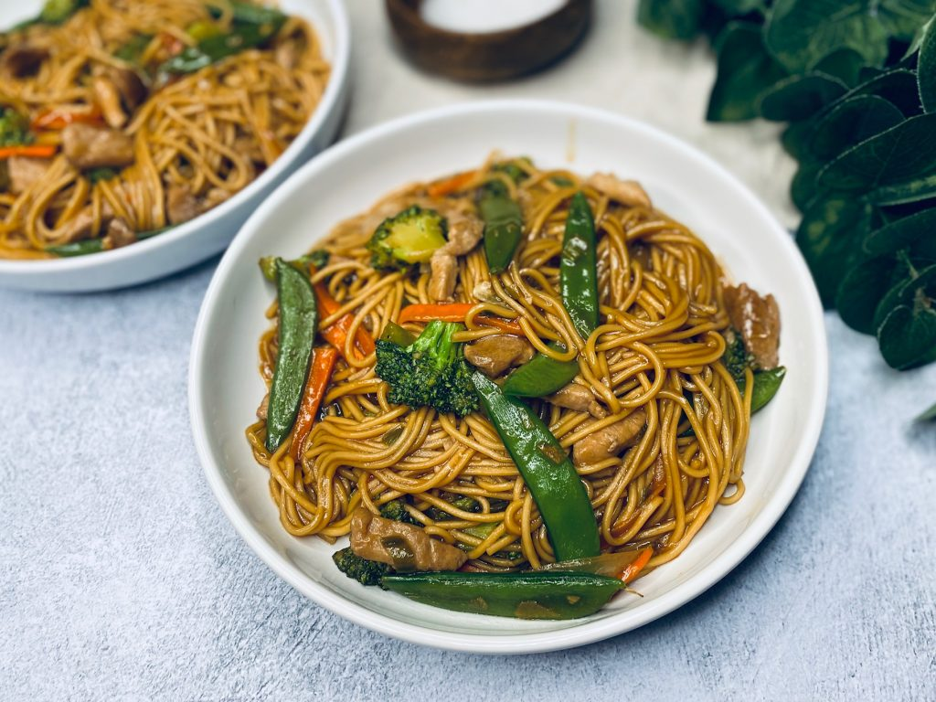 Lo mein noodles with pork in a white bowl