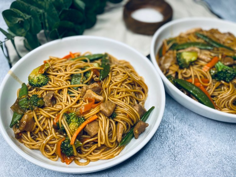 Pork lo mein with broccoli and snow peas in a white bowl