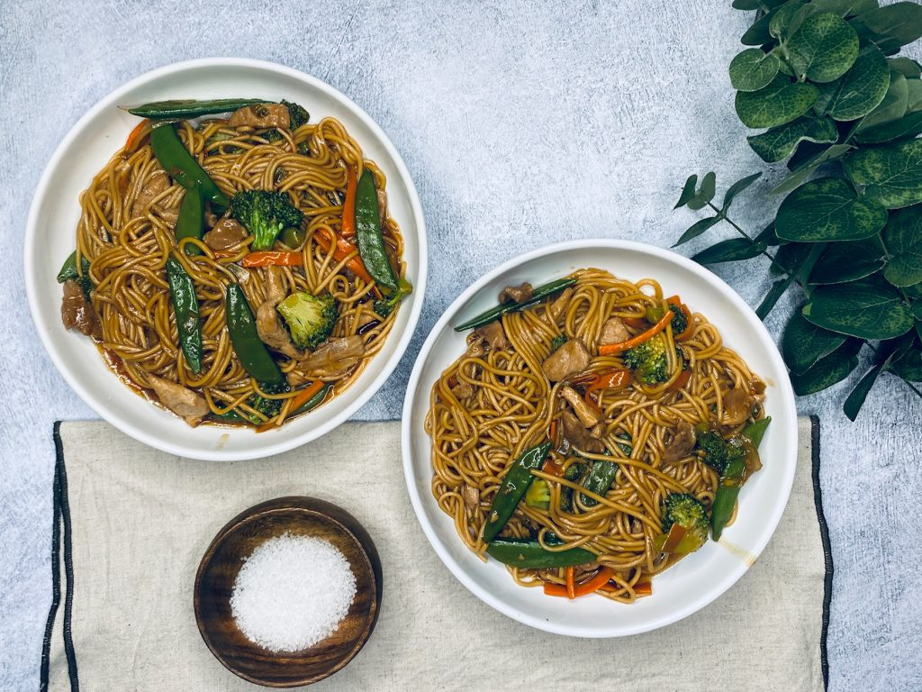 Two bowls filled with pork lo mein