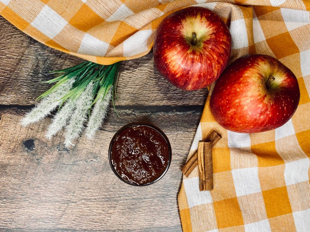 A wooden board with flowers, cinnamon sticks, apples, and a sauce