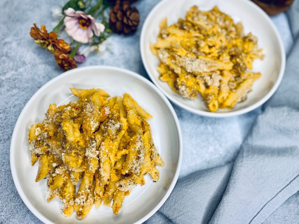 Two white bowls with pasta and butternut squash sauce
