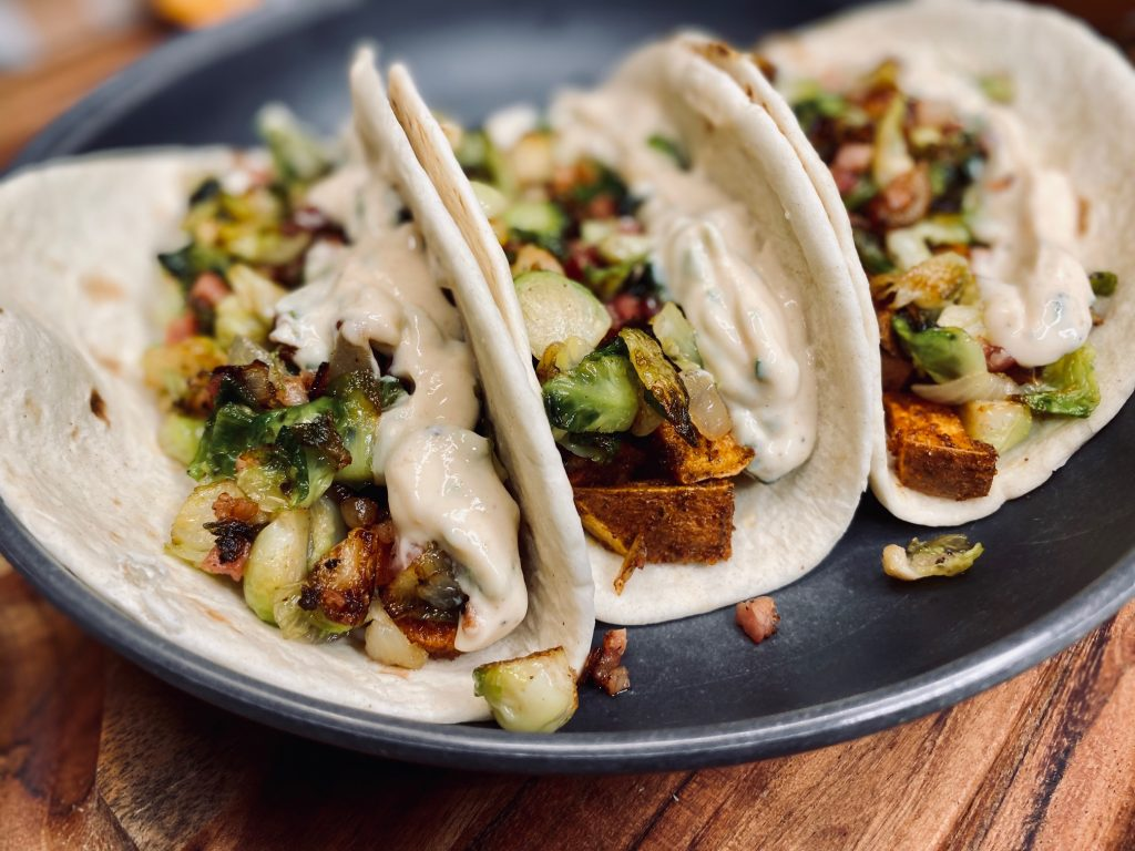 Three tacos filled with sweet potatoes and brussel sprouts