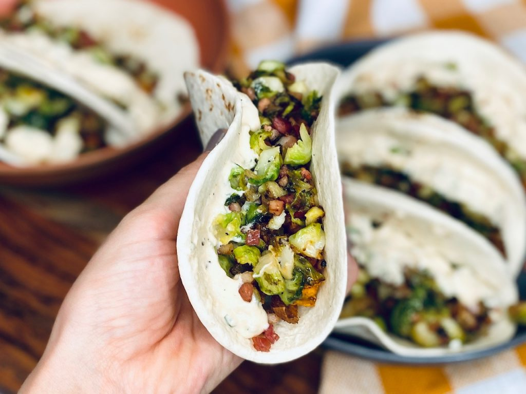 Person holding a taco filled with sweet potatoes and brussel sprouts