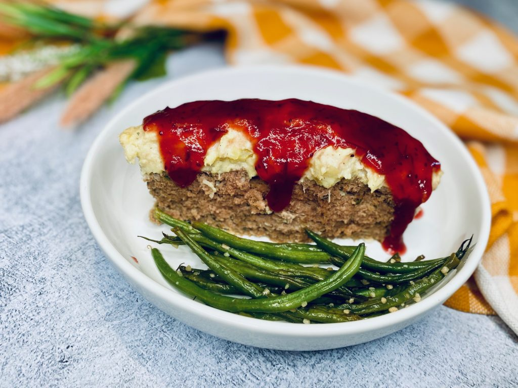 Slice of turkey meatloaf with mashed potatoes and cranberry sauce