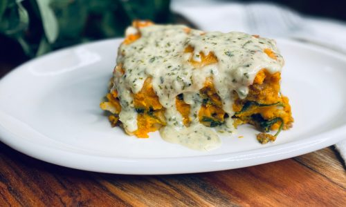 White plate with slice of butternut squash lasagna covered in garlic sauce
